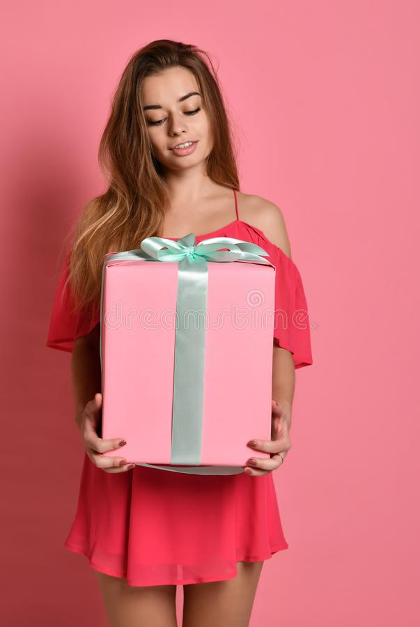 Happy pretty young woman holding gift box stock photography