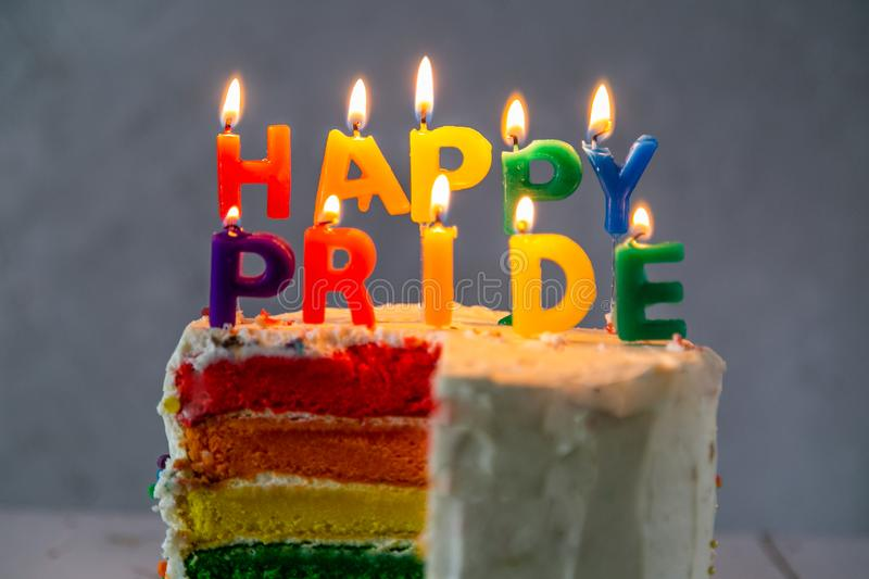 Happy pride day - rainbow layered cake with candles. Tolerance and equality for lgbt community, same sex marriage royalty free stock photos