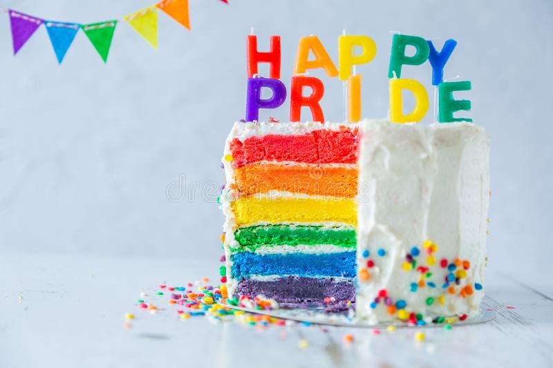 Happy pride day - rainbow layered cake with candles. Tolerance and equality for lgbt community, same sex marriage. Copy space royalty free stock photography
