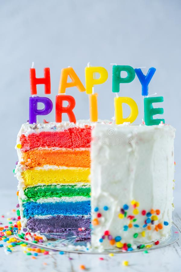 Happy pride day - rainbow layered cake with candles. Tolerance and equality for lgbt community, same sex marriage. Copy space royalty free stock images