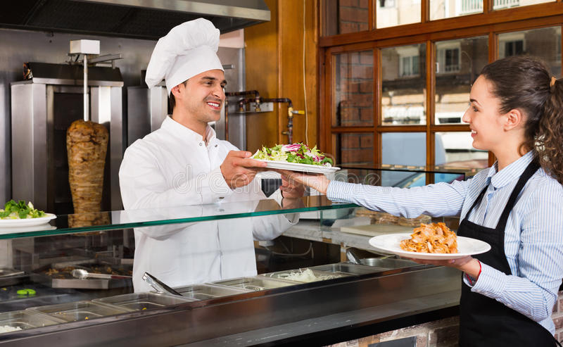 Happy professional chef and young waitress taking kebab for cli royalty free stock photography