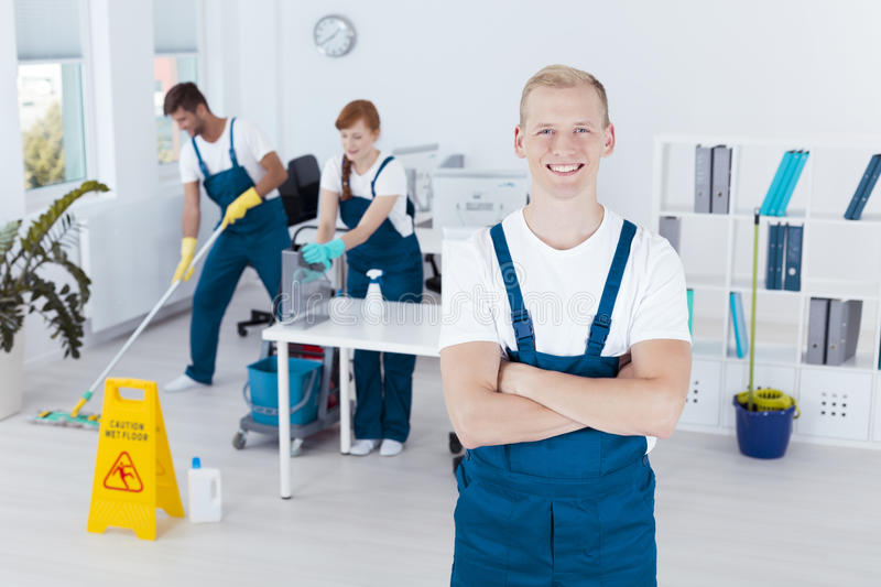 Happy professional cleaner. And two workers cleaning office stock image
