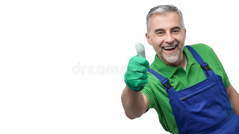 Happy professional gardener giving a thumbs up. Happy professional gardener with green gloves giving a thumbs up royalty free stock image