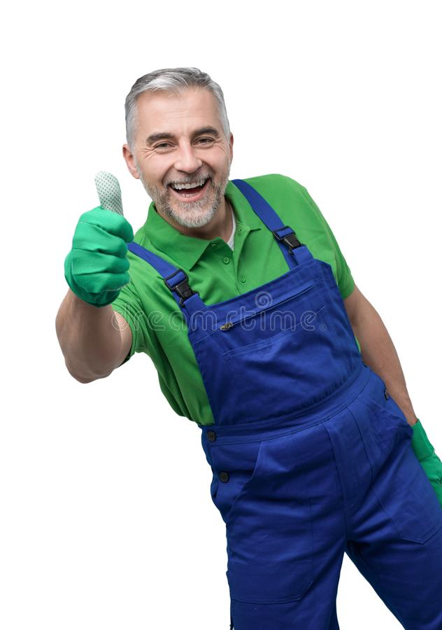 Happy professional gardener giving a thumbs up. Happy professional gardener with green gloves giving a thumbs up stock image
