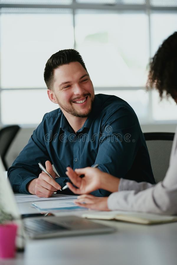 Successful smiling young corporate businessman discussing new business project plan using charts with his colleague royalty free stock photography