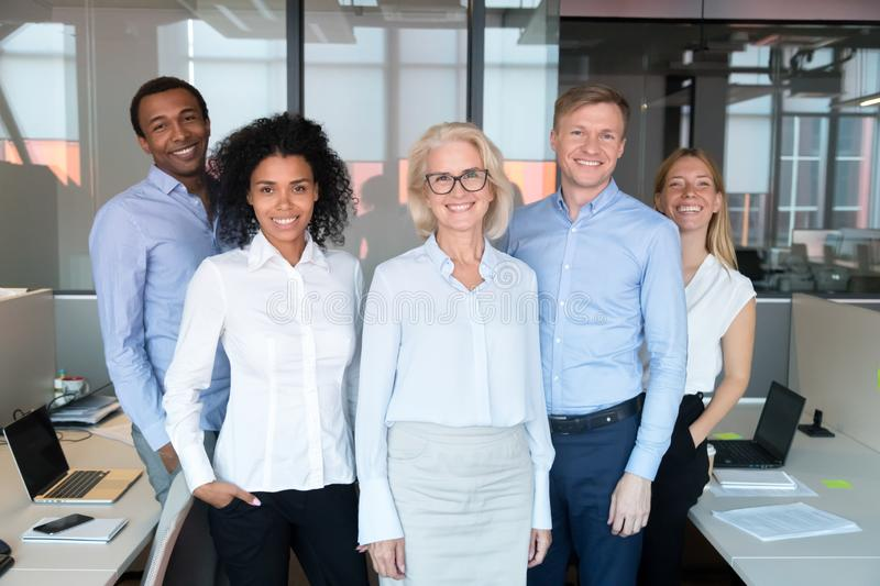 Happy professional team with old female business leader posing together stock photography