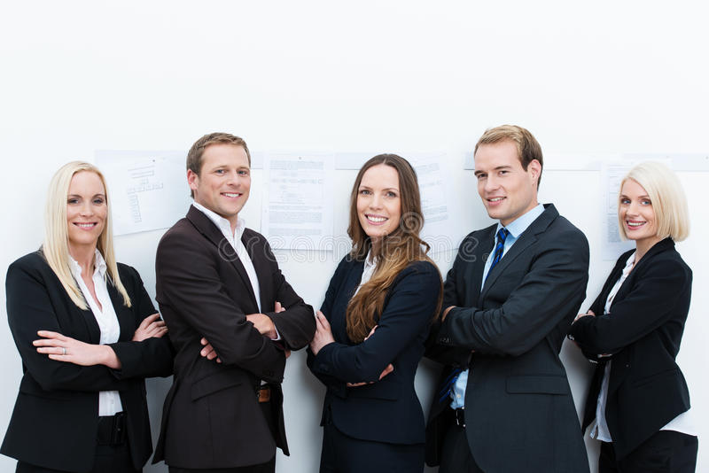 Happy professional team standing with folded arms. Happy professional team made of two businessmen and three businesswomen standing with folded arms, against a stock photos