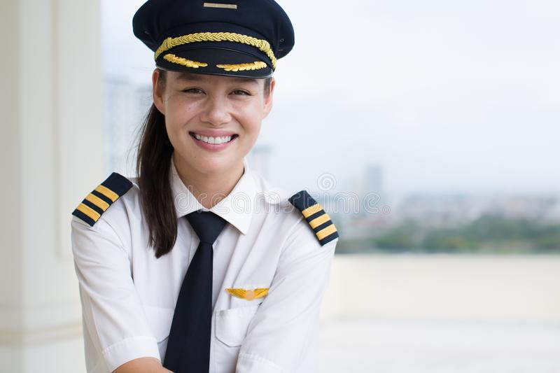 Portrait of a pretty female pilot smiling royalty free stock photography