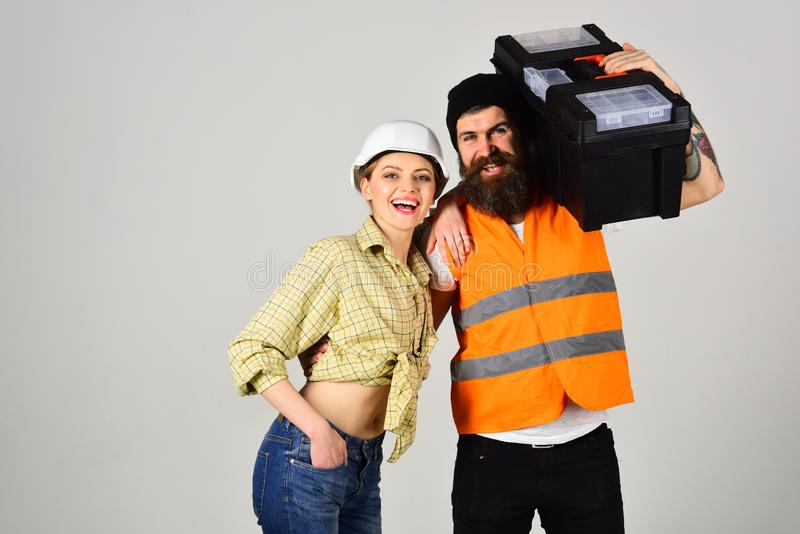 Happy professionals. Couple of hard workers. Pretty woman and bearded man in workwear. Builders or building technicians stock photo