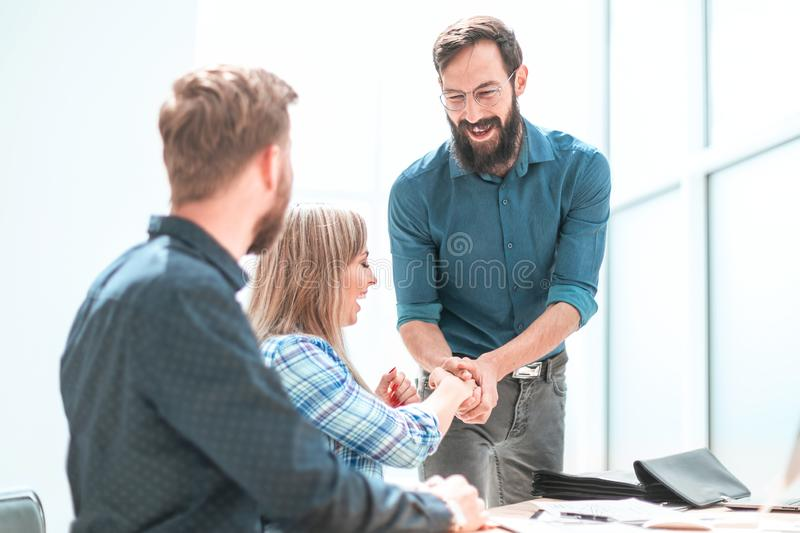 Happy project Manager shaking hands with employee. royalty free stock image