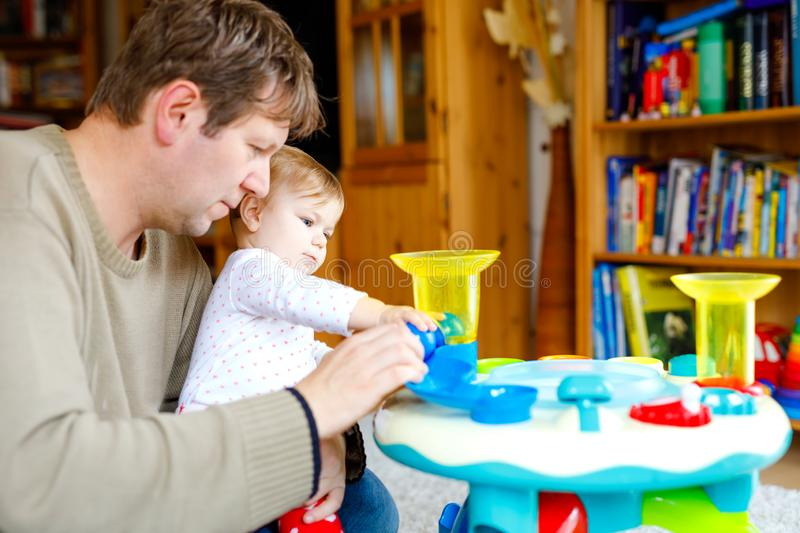 Happy proud young father having fun with baby daughter, family portrait together. Dad playing with baby girl with. Educational sorter toy with different stock image