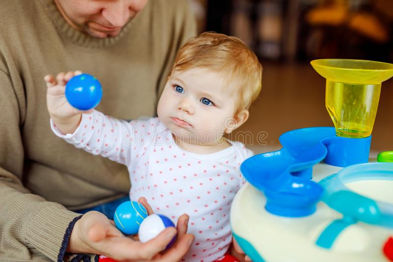 Happy proud young father having fun with baby daughter, family portrait together. Dad playing with baby girl with. Educational sorter toy with different stock photography