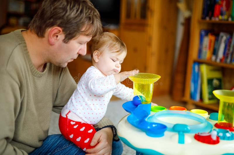 Happy proud young father having fun with baby daughter, family portrait together. Dad playing with baby girl with. Educational sorter toy with different royalty free stock image