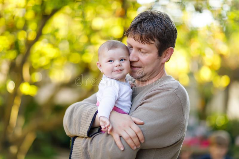 Happy proud young father having fun with newborn baby daughter, family portrait togehter. Dad with baby girl outdoors stock photo