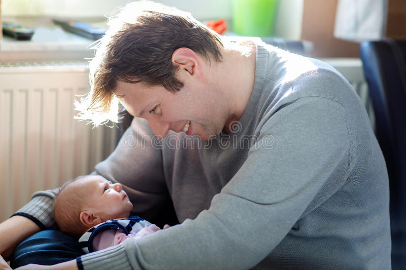 Happy proud young father with newborn baby daughter, family portrait togehter royalty free stock photo