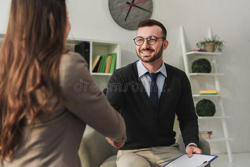 Happy psychologist and patient shaking hands. In doctors office stock photography
