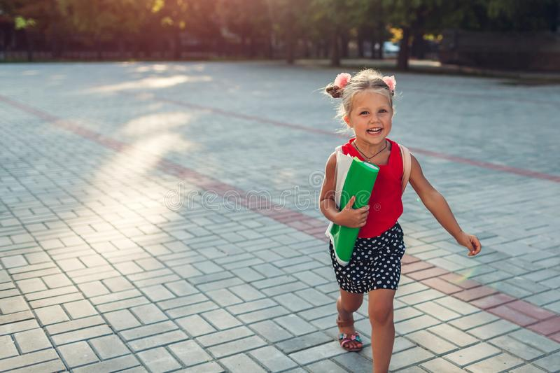 Happy pupil girl running outdoors primary school wearing backpack and holding file. Child is late for lesson royalty free stock photography