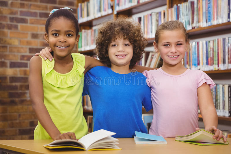 Happy pupils reading a library book. At the elementary school stock image