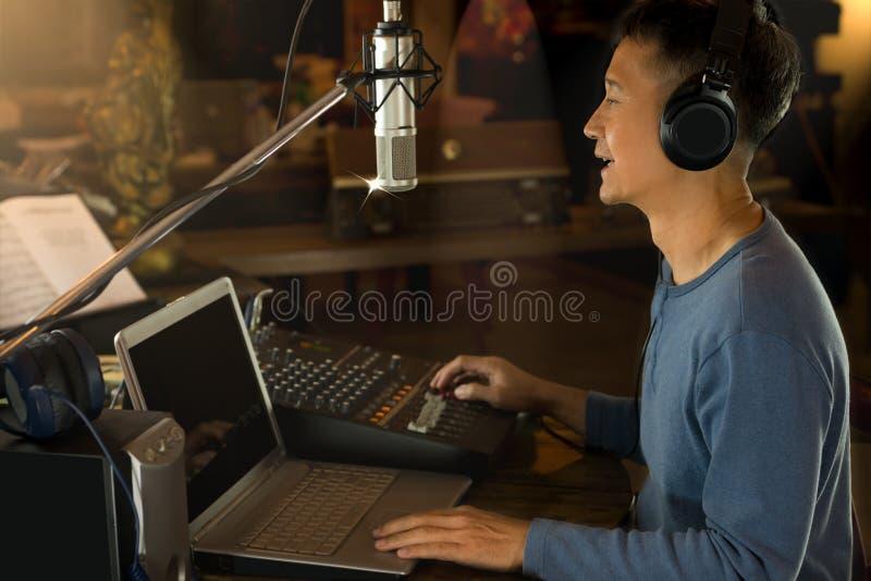 Happy radio broadcaster talking to microphone . Happy radio broadcaster talking to microphone and adjusting volume of audio mixer. DJ greeting his radio royalty free stock images