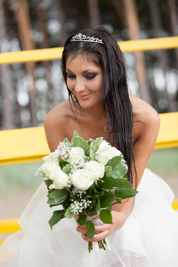 Happy on the rain. Happy bride with bouquet smiling in the rain royalty free stock image