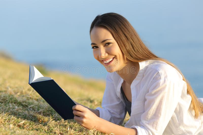 Happy reader holding a book on the grass looks at you. Happy reader holding a paper book lying on the grass looks at you stock images