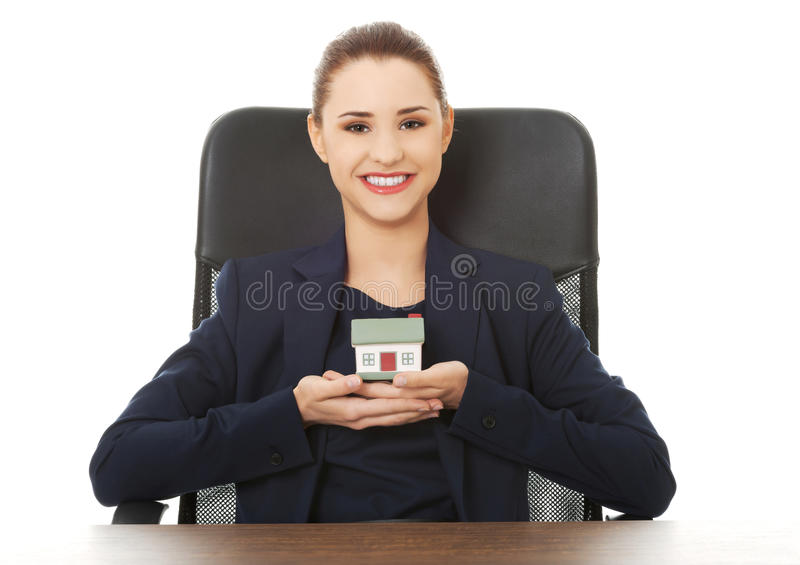 Happy real estate agent, holding a house model stock photos