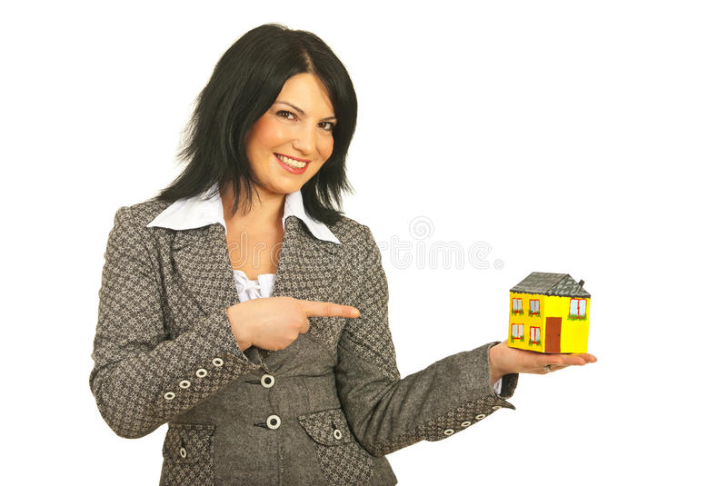 Happy real estate woman pointing. Happy real estate business woman holding and pointing to a miniature house isolated on white background royalty free stock photography