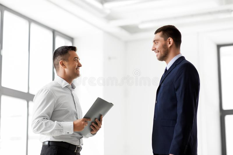 Happy realtor meeting customer at new office stock image