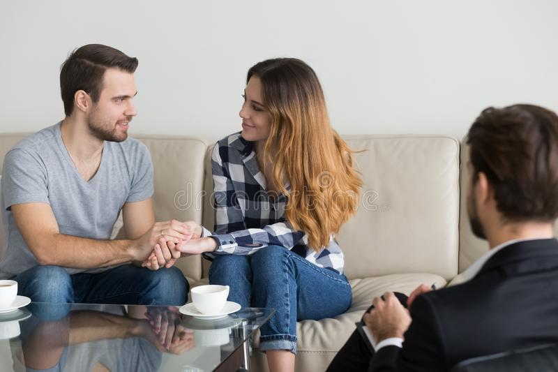 Happy reconciled couple holding hands satisfied with family therapy session. Happy reconciled young couple holding hands satisfied with family therapy session royalty free stock photography