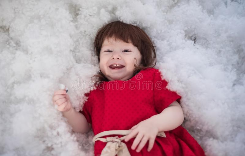 Happy red-haired girl. The baby lies on artificial snow royalty free stock images