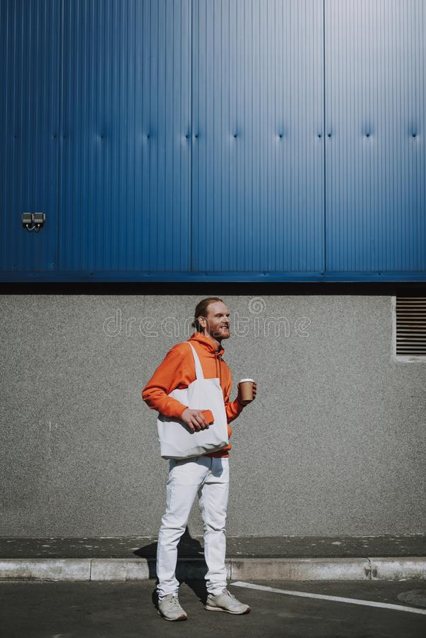 Happy red haired man walking with coffee. Urban lifestyle concept. Full length portrait of young happy red haired hipster man with cup of coffee and mobile phone stock image