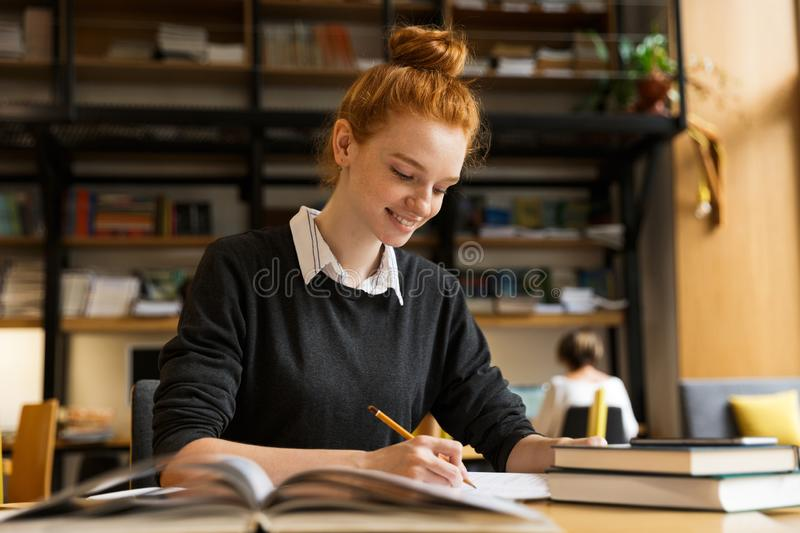 Happy red haired teenage girl studying at the table royalty free stock image