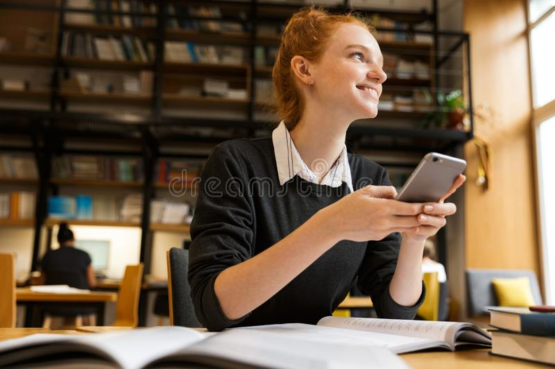 Happy red haired teenage girl studying at the table stock image