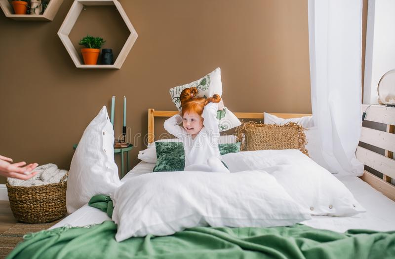 Happy redhead baby girl playing in bed. Little girl with red hair play on the bed wearing pajamas stock image