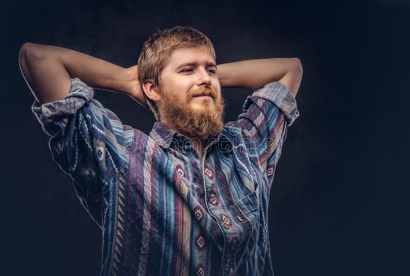 Happy redhead bearded guy dressed in an old-fashioned shirt stretching in a studio on a dark background. Happy redhead bearded guy dressed in an old-fashioned stock images