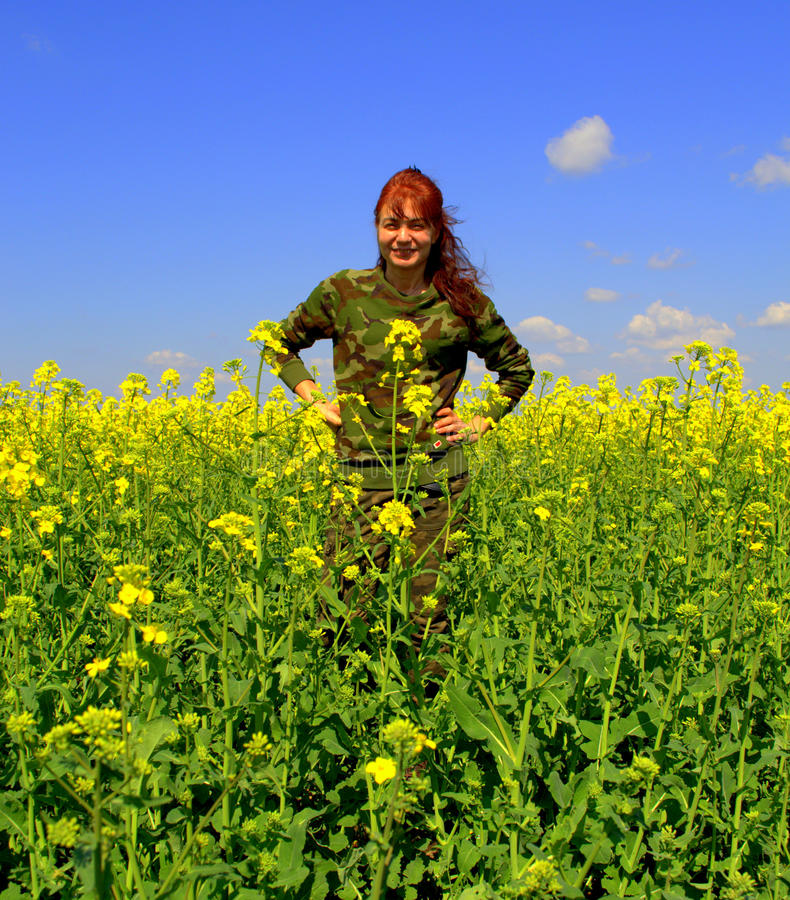 Happy redhead camouflage woman yellow fields. Vivid yellow spring fields against clear blue sky and military style dressed woman in the fields enjoying it stock image