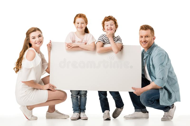 Happy redhead family with two children holding blank placard and smiling at camera. Isolated on white stock images
