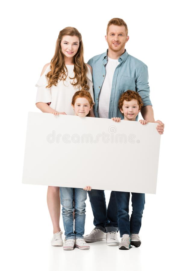 Happy redhead family with two kids holding blank banner and smiling at camera. Isolated on white stock photography