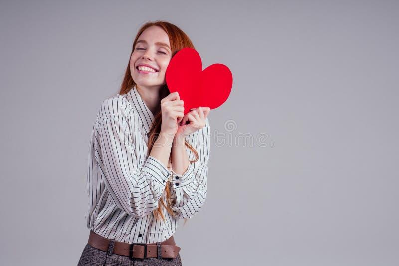 Happy redhead Girl Geschäftsfrau in einem gestreiften Hemdmodell senden Luftkuss mit dekorativen Herzen Valentinstag Geschenk auf stockfoto