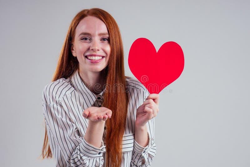 Happy redhead Girl Geschäftsfrau in einem gestreiften Hemdmodell senden Luftkuss mit dekorativen Herzen Valentinstag Geschenk auf lizenzfreie stockfotos
