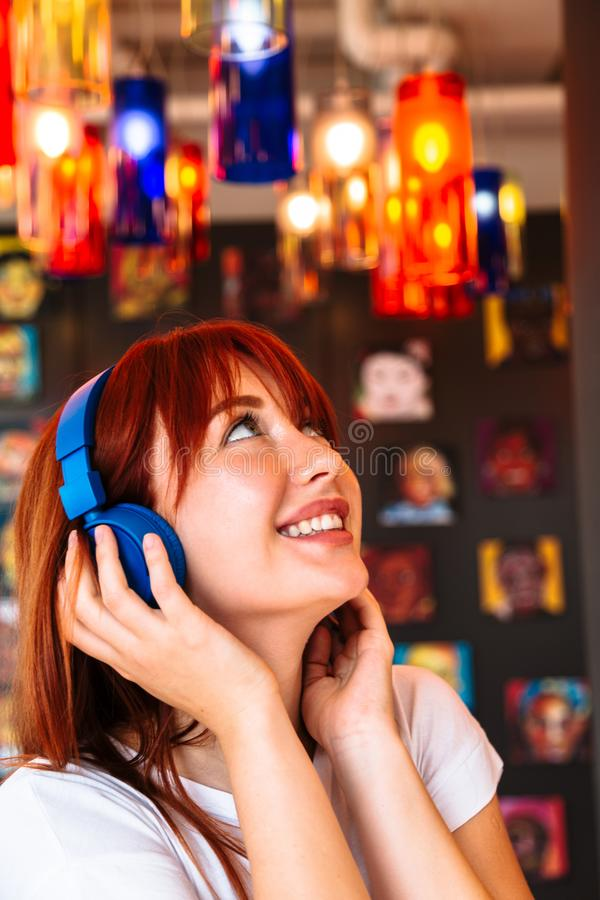 Happy girl listens to music on headphones in cafe royalty free stock image
