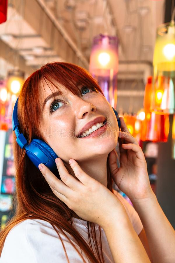 Happy girl listens to music on headphones in cafe stock photography