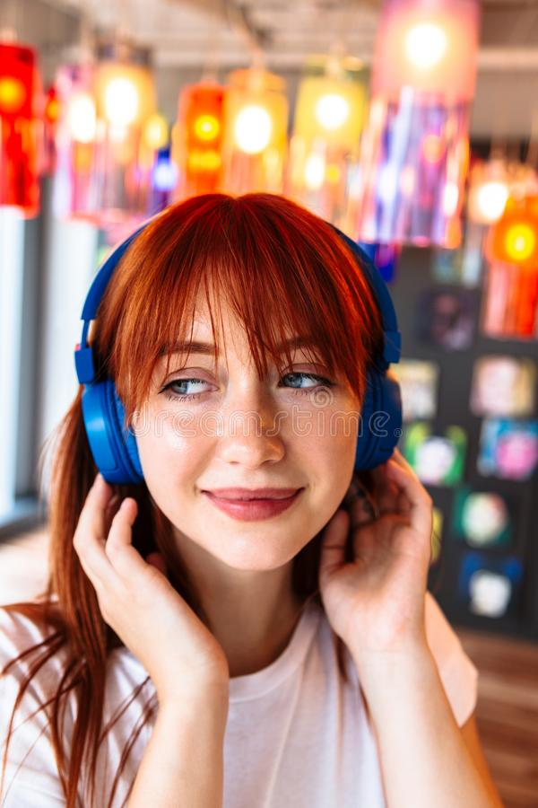 Happy girl listens to music on headphones in cafe stock image