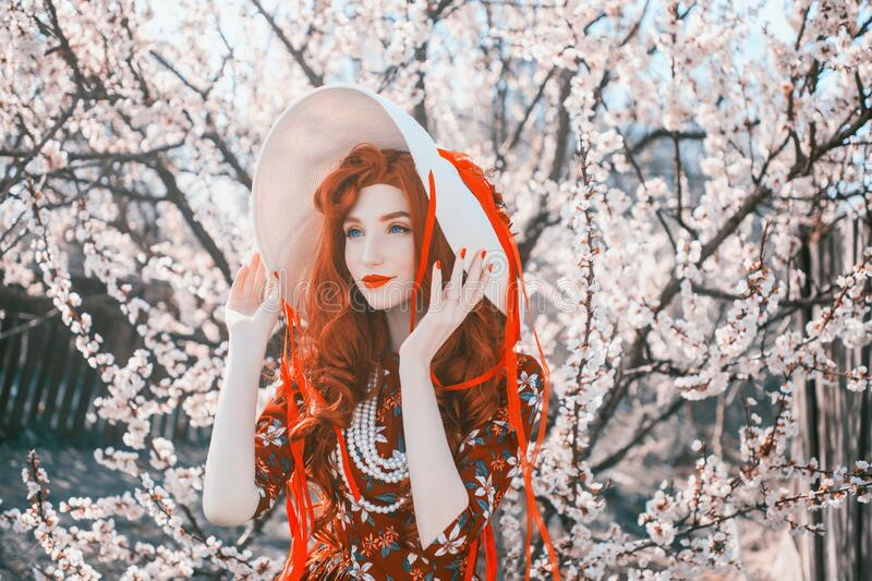 Happy redhead girl in spring flower garden. Valentine day background. Red manicure. Woman portrait in vintage hat and retro dress stock images