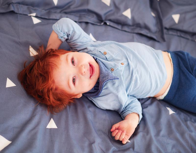 Happy redhead toddler baby having fun in bed royalty free stock photos