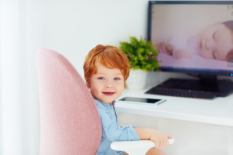 Happy redhead toddler baby boy is sitting in office chair at working place. Smiling redhead toddler baby boy is sitting in office chair at working place royalty free stock images