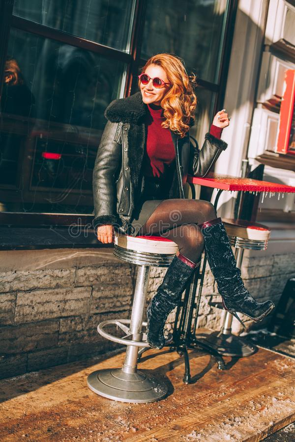 Happy Redhead Woman Laughing in Street Cafe. Fashion Girl in Black Jacket and Red Sunglasses stock image
