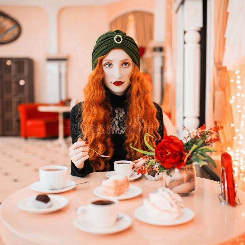 Happy redhead woman with long curly hair in drink hot chocolate in cafe. Girl with smile hold a teaspoon in hand. Hot coffee royalty free stock photos
