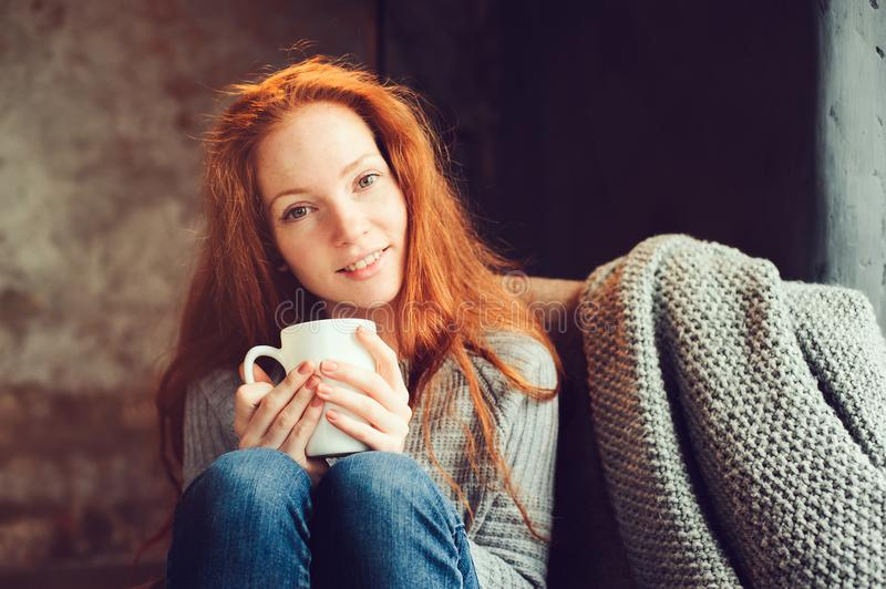 Happy redhead woman relaxing at home in cozy winter or autumn weekend with book and cup of hot tea, sitting in soft chair. With blanket stock image