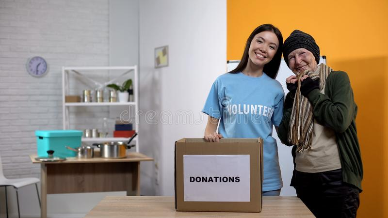Happy refugee and volunteer smiling camera, receiving clothes homeless center stock image